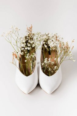 Heeled shoes with blooming gypsophila flowers on white stock vector