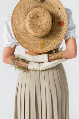 Partial view of woman in gloves with flowers and straw hat behind back isolated on white stock vector