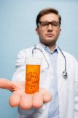 bottle with painkillers in hand of doctor on blurred background isolated on blue