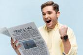 vzrušený mladý muž v košili čtení cestovní noviny a radovat se izolované na modré