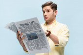 confused young man in shirt reading travel newspaper isolated on blue