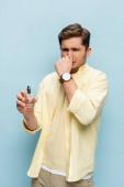 angeekelter junger Mann in gelbem Hemd mit Flasche mit Parfüm und verdeckter Nase auf blauem Grund