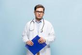 lékař v bílém plášti a brýle drží podložku a dívá se na fotoaparát izolované na modré