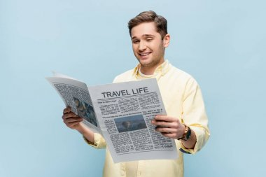Pleased young man in shirt reading travel newspaper isolated on blue stock vector