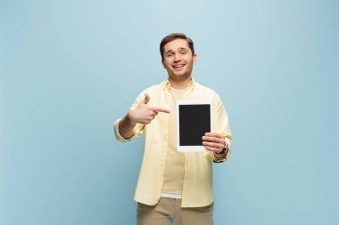 Happy young man in yellow shirt pointing with finger at digital tablet with blank screen isolated on blue stock vector