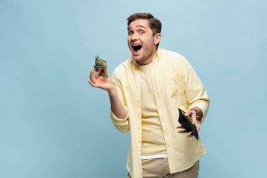 Amazed young man in yellow shirt holding wallet with dollars isolated on blue stock vector