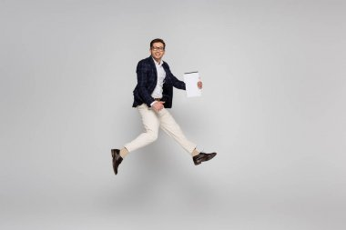 Full length of cheerful businessman in glasses holding paper while jumping on grey stock vector
