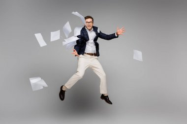 Full length of happy businessman jumping near papers in air on grey stock vector