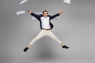 Full length of cheerful businessman jumping near papers in air on grey stock vector