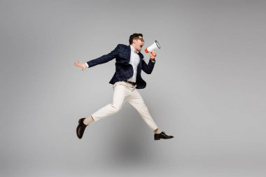 Full length of businessman jumping and screaming in megaphone on grey stock vector