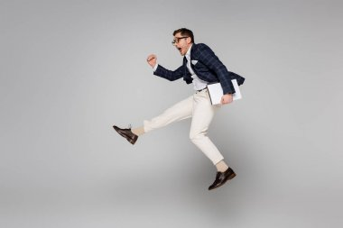 Full length of amazed businessman holding paper folder while flying on grey stock vector