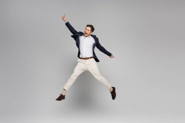 Full length of excited young man with outstretched hands levitating on grey stock vector