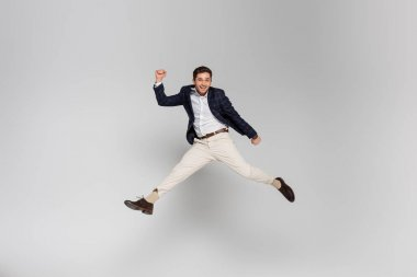 Full length of happy young man with clenched fists levitating on grey stock vector