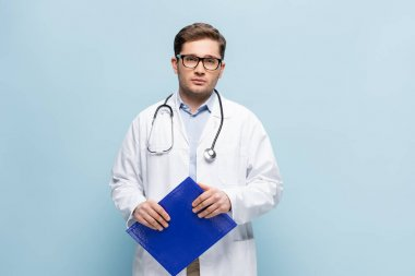 Doctor in white coat and glasses holding clipboard and looking at camera isolated on blue stock vector