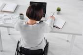 Freiberufler im Rollstuhl schreiben auf Notebook in der Nähe von Laptop und Papier