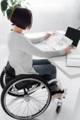 Seitenansicht einer behinderten Frau, die mit Diagrammen auf Papieren in Laptopnähe arbeitet