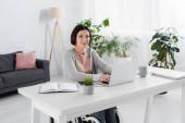 Handicapped žena ve sluchátkách pomocí notebooku doma