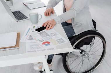 Cropped view of disabled freelancer taking smartphone near laptop and documents on table stock vector
