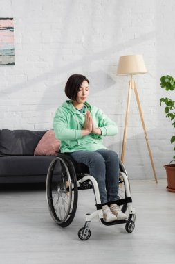 Woman in wheelchair sitting with praying hands at home stock vector