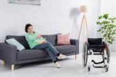 Fröhliche Frau mit Fernbedienung und Popcorn vor dem Fernseher im Rollstuhl