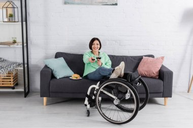 Smiling woman with glass of wine watching tv near burger and wheelchair in living room stock vector