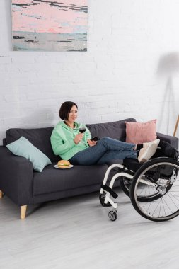 Happy handicapped woman with glass of wine watching movie near hamburger on couch and wheelchair stock vector