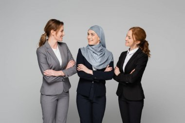 Cheerful businesswomen looking at muslim colleague isolated on grey stock vector