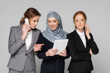 Businesswoman pointing with finger at arabian colleague with digital tablet while talking on cellphone isolated on grey stock vector