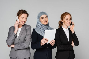 Cheerful businesswomen talking on smartphones near muslim colleague with digital tablet isolated on grey stock vector