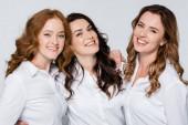 Dospělé ženy v bílých košilích s úsměvem na kameru izolované na šedé