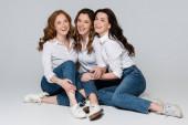 Positive Frauen lachen auf grauem Hintergrund