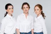Frauen mit Augenklappen blicken vereinzelt auf graue Kamera