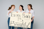 Smiling women looking at each other while holding placard with every body is beautiful lettering isolated on grey