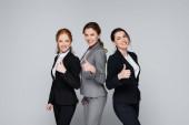 Usmívající se podnikatelky ukazují jako gesto izolované na šedi