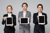 Businesswomen holding digital tablets with blank screen isolated on grey