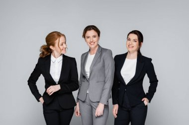 Smiling businesswomen with hands in pockets isolated on grey stock vector