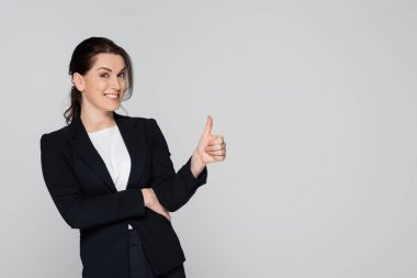 Businesswoman showing thumb up and smiling at camera isolated on grey stock vector