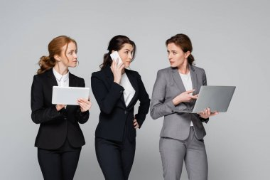 Businesswomen in formal wear using gadgets isolated on grey stock vector