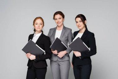 Positive businesswomen holding paper folders isolated on grey stock vector