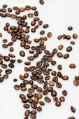 čerstvá a hnědá kávová zrna na bílém pozadí