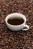 bílý šálek s připravenou kávou na hnědých fazolích