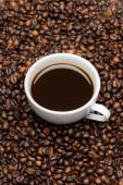 vysoký úhel pohledu na bílý šálek s připravenou kávou na hnědých fazolích
