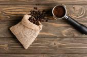vrchní pohled na pytel s fazolemi v blízkosti kovového portafiltru s čerstvou mletou kávou na dřevěném povrchu