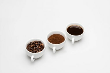 Mugs with prepared and ground coffee near beans on white stock vector