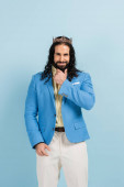 bärtiger hispanischer Mann in Krone und Jacke lächelt isoliert auf blauem Grund