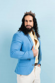 bearded hispanic man in crown and jacket posing isolated on blue