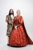 full length of historical interracial couple in crowns and medieval clothing on white