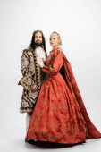 full length of historical interracial couple in crowns and medieval clothing standing on white