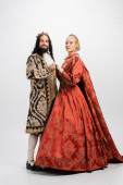 full length of historical interracial couple in royal crowns and medieval clothing on white