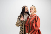 hispanic king in crown and medieval clothing looking at blonde wife isolated on white